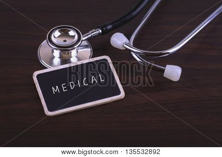 Medical Concept- MEDICAL words written on label tag with Stethoscope on wood background