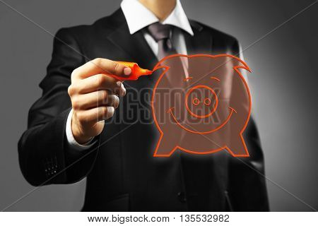 Businessman drawing piggy bank on virtual screen