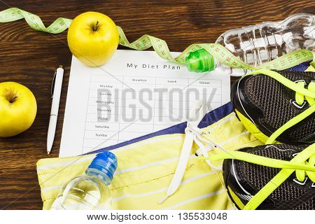 Sports items: sneakers headphones and shorts on the wooden background