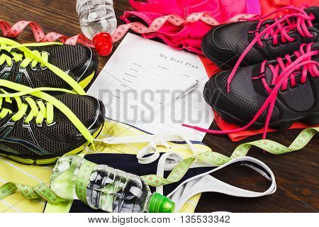 Sports items: sneakers headphones and sports bra on the wooden background