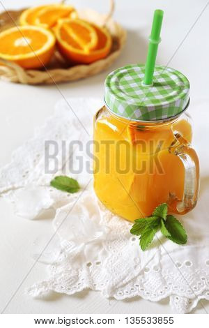 Orange juice in glass jar and oranges