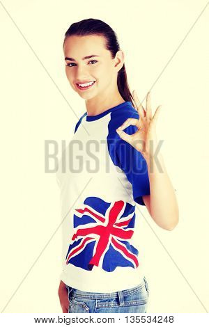 Beautiful young teenage woman showin ok gesture.