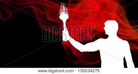 Low angle view of sportsman holding a torch against different black silhouette