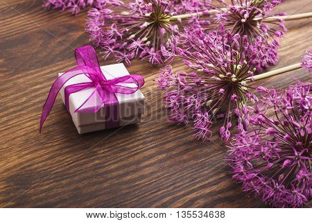 Puffy violet alliums and a little present on the wooden background