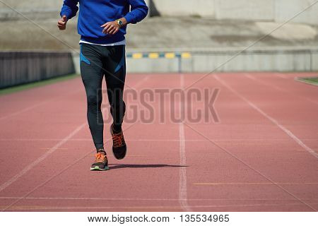 Athlete runner running on athletic track field
