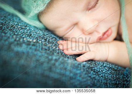 newborn baby sleeping sweetly on a blue rug in blue cap