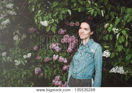 Portrait of a beautiful smiling, young woman outdoor with blossom purple lilac flowers in a spring garden. Attractive female in casual jeans clothes. Spring concept, nature and care.