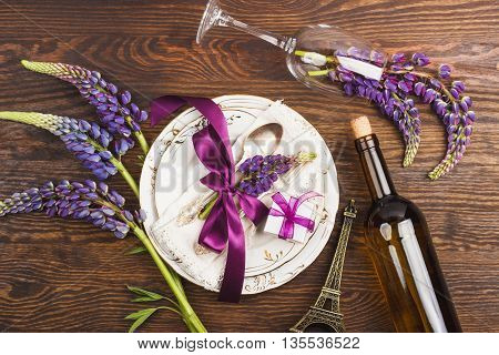 Tableware with violet lupinus silverware and decorations on the wooden background