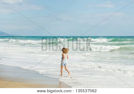 Young woman in blue denim jumpsuit walking towards stormy sea