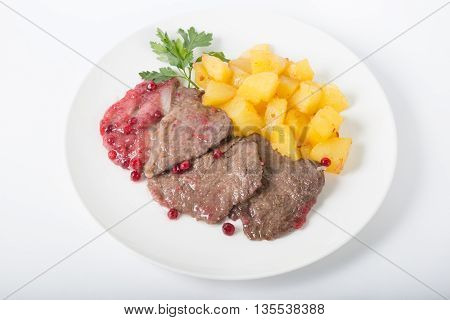 Steak with cranberry sauce served with potato garnish