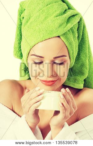 Woman in bathrobe with cream