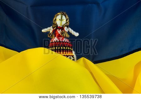 Handmade textile doll, Rag dolls handmade Motanka in ethnic style on the background of the flag of Ukraine. Motanka - Ukrainian folk doll protecting the family home