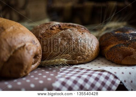 Homemade round bread roll with poppy seeds and whole grain bread on a checkered tablecloth