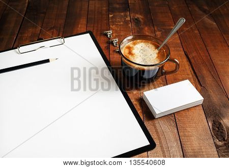 Close-up of blank paperwork template. Blank stationery set on vintage wooden table background. Paper blank letterhead coffee cup and pencil. Mock-up for design portfolios. Top view.