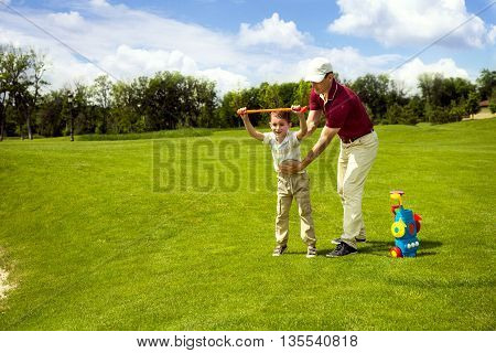 Father with son are training at golf course. Man teaching his son to play mini golf. Concept of friendly family
