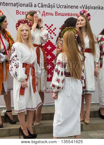 CHISINAU, MOLDOVA - MAY 19: Young beautiful girls in national costumes and wreaths on the heads at the International Day of Embroideries on May 19, 2016 in Chisinau, Moldova.