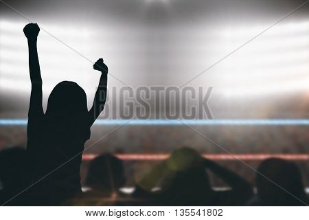 Silhouettes of football supporters against focus on foreground of ropes in a boxing ring