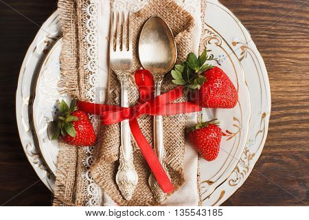 Tableware and silverware with red ripe strawberries on the wooden background