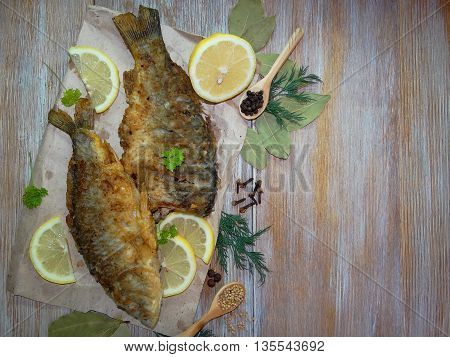 fried fish carp , lying on wooden boards with lemon and spices