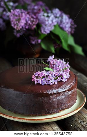Homemade chocolate cake decorated with lilac on a wooden background