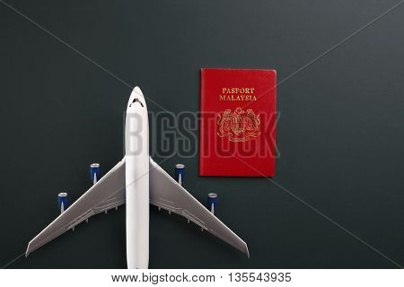 malaysia passport and toy plane
