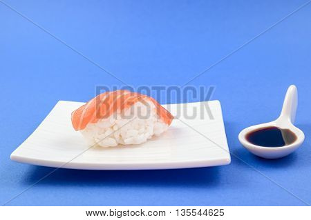 sushi and soy sauce on blue background