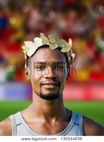 Portrait of victorious sportsman with crown of laurels against blurry football pitch with crowd