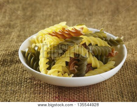 fusilli pasta on top of sack cloth