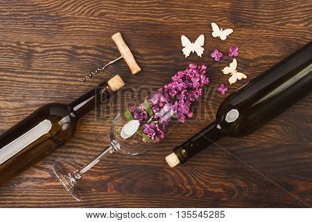 Wineglass with lilacs bottles and butterflies decorations on the wooden background