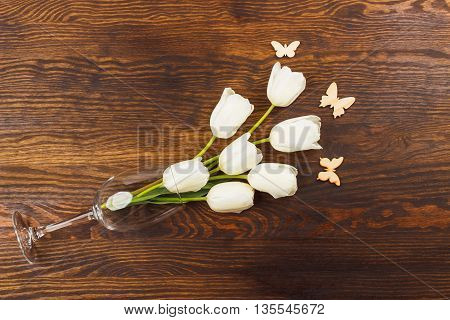 Wineglass with bouquet of white tulips and butterflies decorations on the wooden background