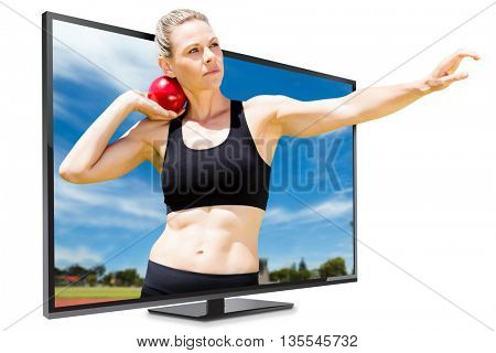 Front view of sportswoman practicing shot put against view of running track