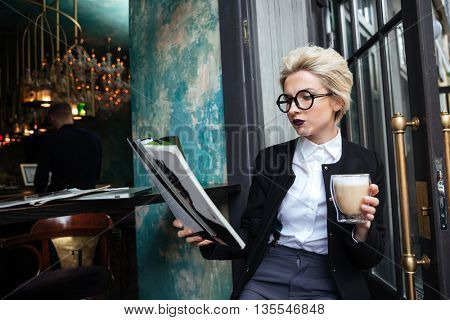 Close-up portrait of a beautiful stylish girl sitting in cafe with cup of coffee and reading magazine outdoors