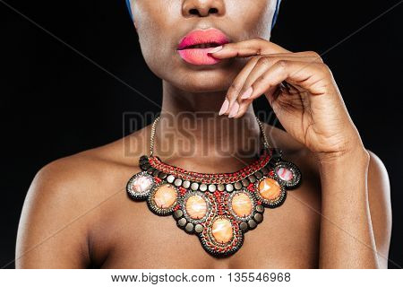 Cropped image of a attractive african woman with her hand on lips isolated on the black background