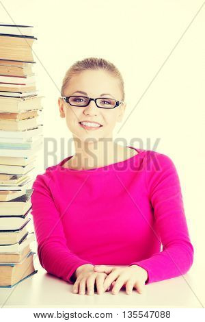 Young happy student with stack of books.