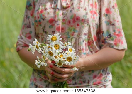woman holding bouquet of daisy blossoms in park