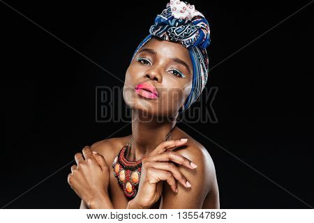 Close-up portrait of a beautiful african woman in shawl on head posing isolated on the black background