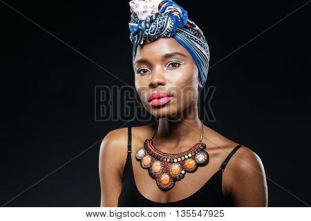 Portrait of a young afro american woman wearing a blue headscarf isolated on the black background