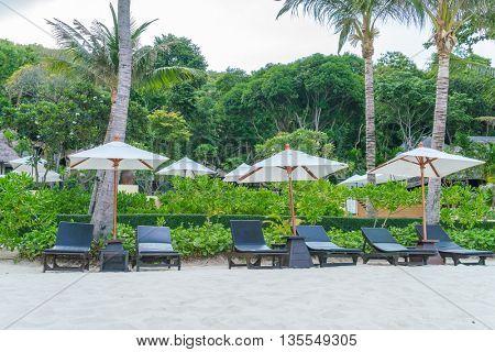 Beautiful beach chairs with umbrella on tropical white sand beach