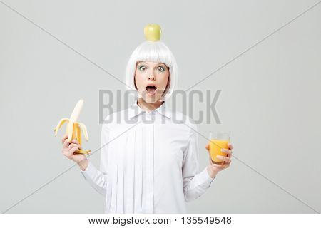 Wondered young woman with apple on her head holding banana and glass of juice