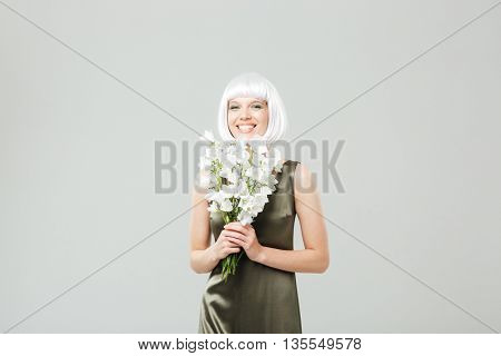 Cheerful young woman with bouquet of flowers standing and laughing