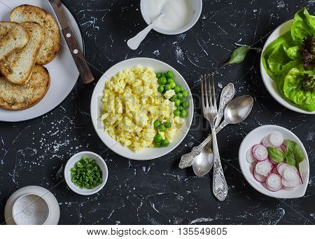 Ingredients for breakfast toast - egg's scramble toasted bread radishes green peas. On a dark stone background. Delicious healthy food