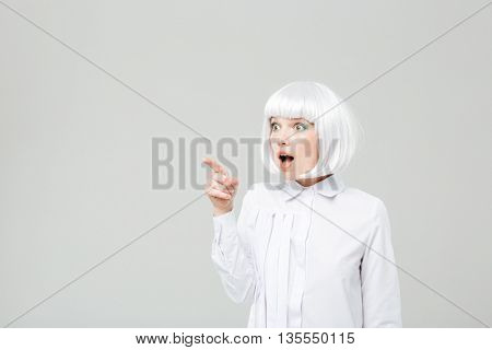 Surprised attractive young woman with opened mouth pointing away