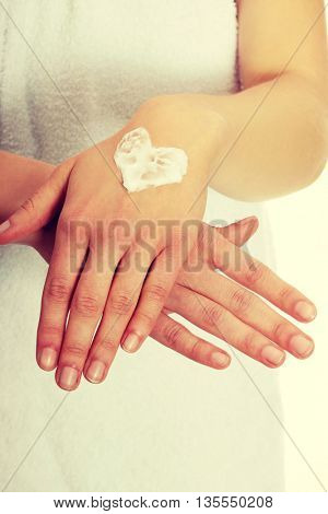 Woman with heart shape cream on hand.