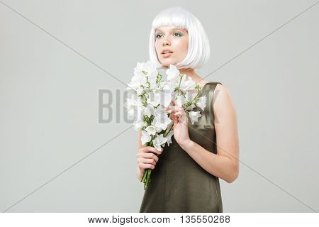 Pensive beautiful young woman with bouquet of flowers
