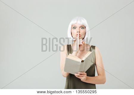 Pretty young woman showing silence sign and reading a book