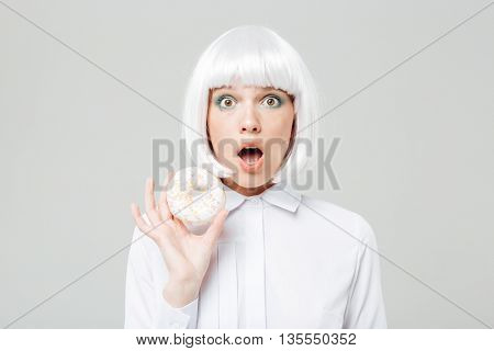 Amazed cute young woman in blonde wig holding donut