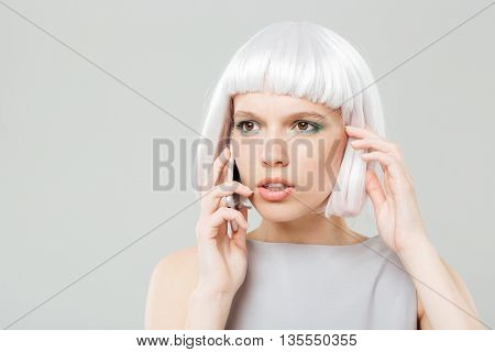 Thoughtful worried young woman in blonde wig talking on mobile phone