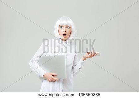 Amazed shocked young woman holding laptop and cell phone