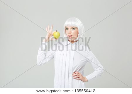 Happy attractive young woman with blonde hair holding fresh apple
