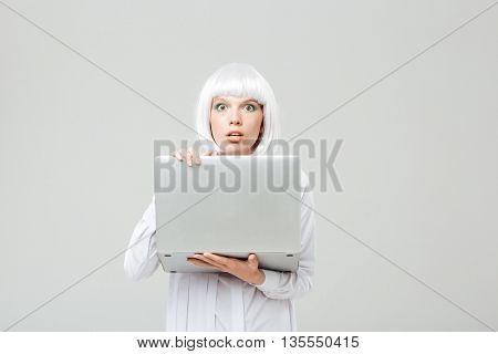 Shocked young woman standing and holding laptop